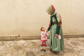 A mother and her daughter walking on a street in Istanbul.