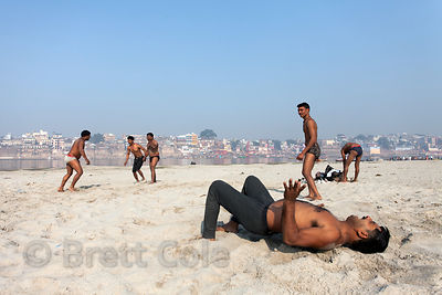Men wrestle in the sand on the banks of the Ganges River, Varanasi, India.