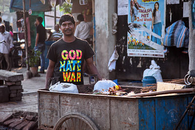"A worker wearing a t-shirt reading ""God Hate War"" collects garbage in a cart in Esplanade, Kolkata, India."