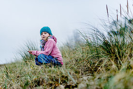 Little Danish girl in a blue hat at the beach in autumn 3