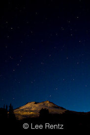 Mt. Baker lit by a setting full moon just before dawn with the Big Dipper, North Star, and other stars shining above, viewed ...