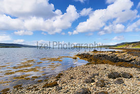 Sea views on a sunny day from a pebble beach at Uiginish Point near Dunvegan on the Isle of Skye, Scotland, UK.
