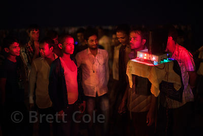 Visitors watch an illuminated demonstration of some sort (a sales operation to be sure) at night on Juhu Beach, Mumbai, India.