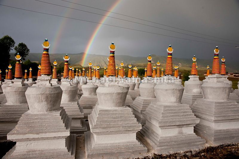 Colorful Stupas (Chorden, in Tibet) in Bame, Sichuan Province stand at attention, as if in awe of the fortuitous double rainb...