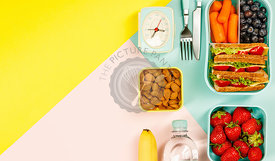 Creative flat lay with healthy lunch and office or school supplies