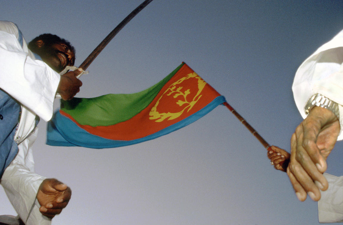 Photo: Sami Sallinen.24 May 1998..The Eritrean flag and a sword are displayed by marchers during Eritrea's Independence Day celebrations. Eritrea won its 30 year war of liberation against Ethiopia on 24 May 1991 and formally became Africa's newest state on 24 May 1993.