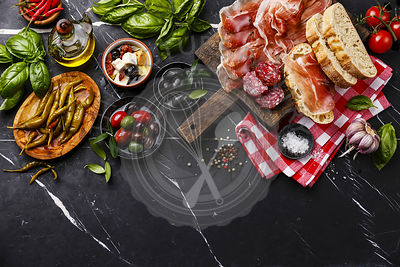 Italian snacks food with Ham, Sliced bread Ciabatta, Olives, Feta cheese with dried tomatoes, Garlic, Sausage and Pepperoni pepper on dark marble background copy space