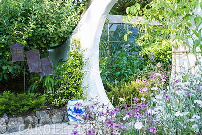 Moon gate framed by Geranium palmatum, Lychnis coronaria Oculata group, and Trachelospermum asiaticum, with copper 'talking h...