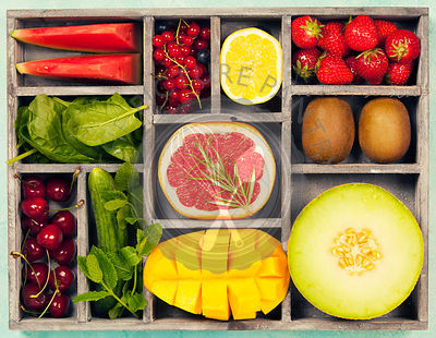Vegetables and fruits in wooden box for vegan, gluten free, allergy-friendly, clean eating and raw diet. Blue background and ...