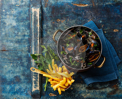 Mussels in copper cooking pan and french fries on blue background