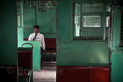 Man on a train near the Lake Gardens Railway Station, Kolkata, India.