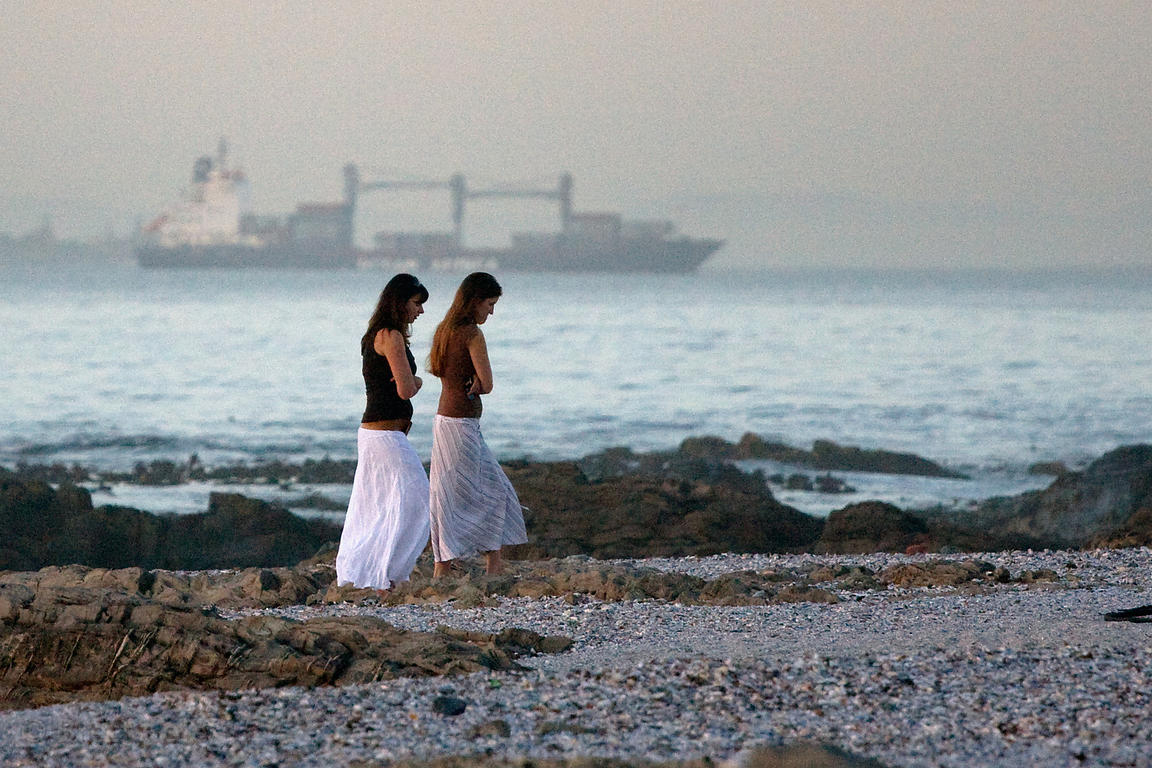 Two women walk on the beach at dusk in Seapoint, Cape Town, South Africa, with a large ship in the distance