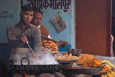 A boy works over hot steam from his wok, Pushkar, Rajasthan, India