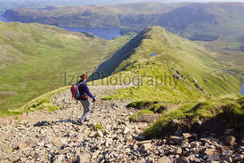 A female hiker walking down Long Stile towards Rough Crag and Haweswater in the Lake District.