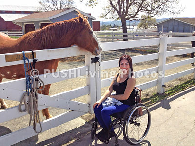 Young woman in a wheelchair with her horse