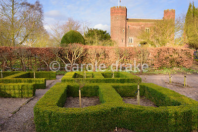 Box parterre with standard roses and gatehoue beyond at Hodsock Priory, Blyth, Notts
