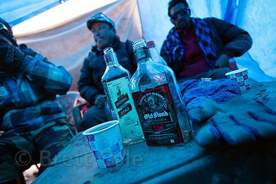 ATV drivers drink whiskey to pass the time during a blizzard on Rohtang Pass, Manali, India