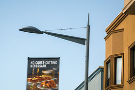 A billboard and a lamp post in front of new townhouses at the Stockyards