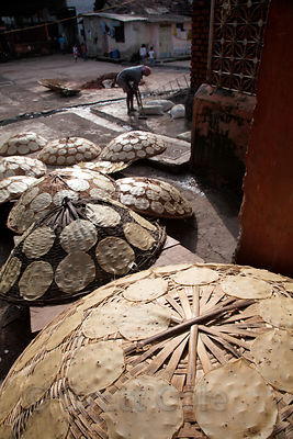 Flatbread dries on large woven baskets in the Dharavi slum, Mumbai, India. I was told it was potato bread.