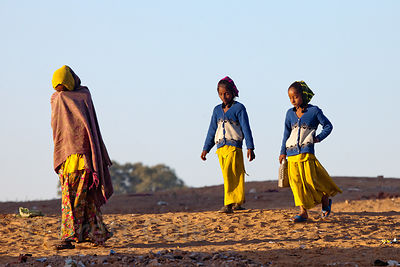 Two girls and their mother walk the mela ground in early morning, Pushkar, Rajasthan, India