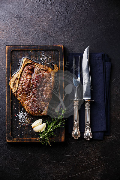 Grilled meat barbecue steak Blade on bone with knife and fork carving set on dark background