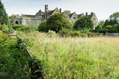 View from cherry orchard across the Daffodil Field to the house and garden. Rodmarton Manor, Rodmarton, Tetbury, Glos, UK