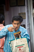 India - Delhi - A man eats street food at the Ashok Chat Corner in Chawri Bazaar