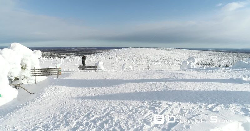 Man Hiking, Snowy Mountain, 4k Aerial View Bypassing a Man Taking Pictures on the Top of a Fjeld Tunturi, Full of Snow Covere...