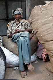 Man working at a shop where cotton is milled and then stuffed into mattresses, Jodhpur, Rajasthan, India