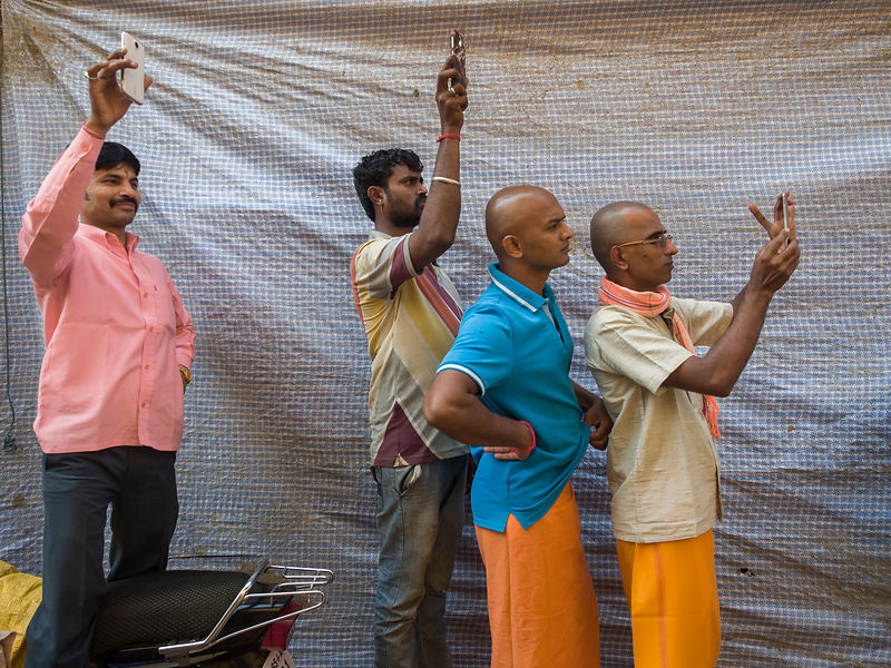 A group of men take pictures during a procession in Varanasi