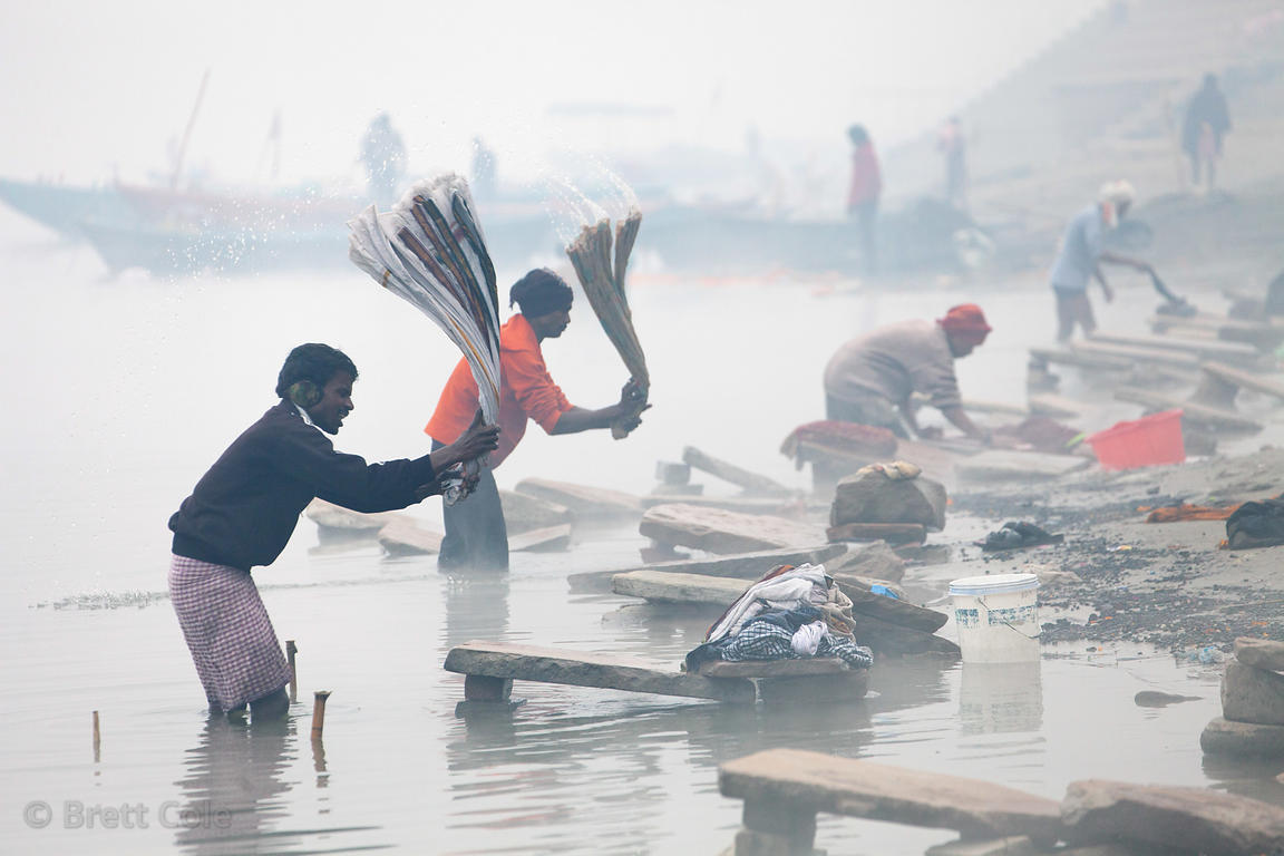 Workers beat laundry against stones at a Dhobi Ghat along the Ganges River on a foggy winter morning, Varanasi, India.