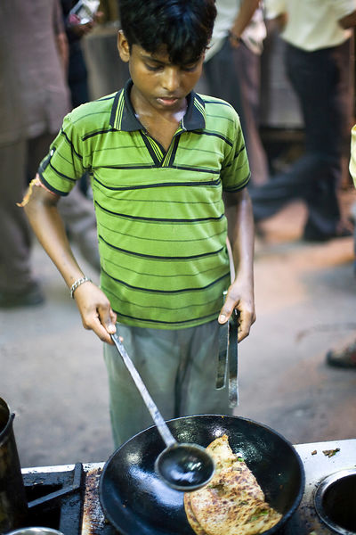 India - Delhi - A boy cooks a paratha in a pan of oil at the famous Parawthe Wala restaurant in Old Delhi