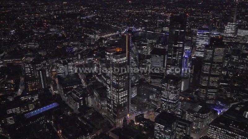 Aerial footage of the skyscraper of the City of London lit up at night