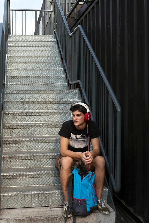 UK - London - A young man wearing headphones, listens to music on the steps of the Boxpark - a so-called 'pop up mall' compri...