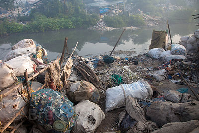 Piles of assorted recycling along a creek in Dhapa, Kolkata, India. Dhapa is the site of Kolkata's main landfill, and a large...