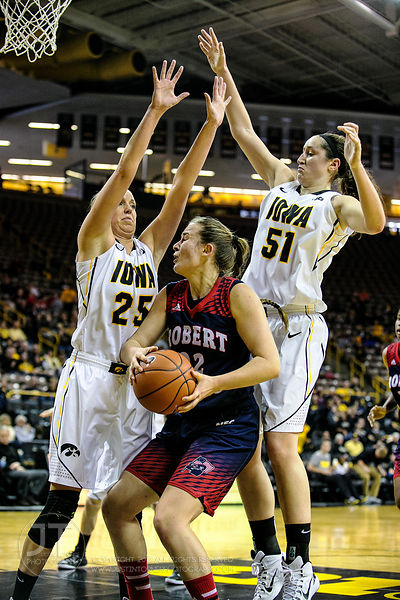 Robert Morris' Megan Smith (22) drives between Iowa's Kali Peschel (25) and Bethany Doolittle (51) during the first half of p...