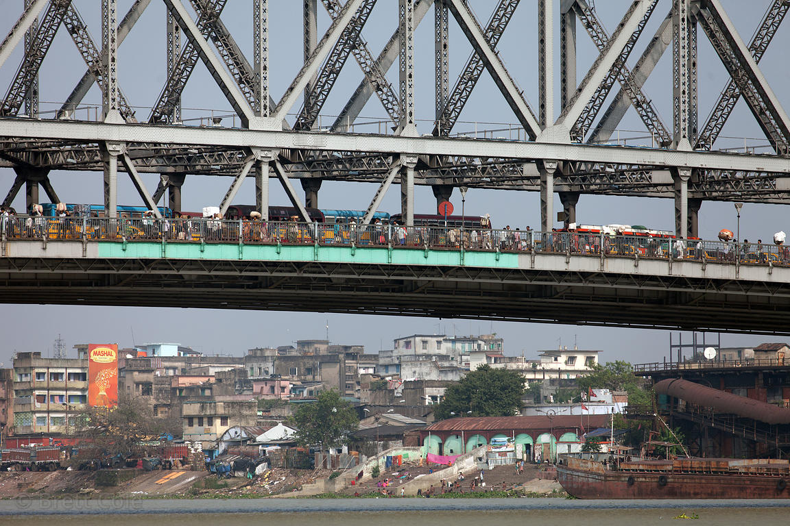 Heavy traffic (both vehicular and foot) on Howrah Bridge in Kolkata, India. Below is the Hooghly River.