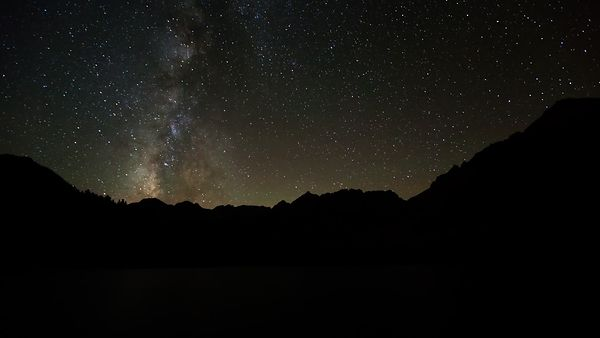 Medium Shot: Heavenly Milky Way Gives Way To Moon Rays & A Serene Mountain Top Lake