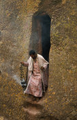 Priest at St. George church, a rock-hewn monolith below ground level in the shape of a crucifix, Lalibela, Ethiopia