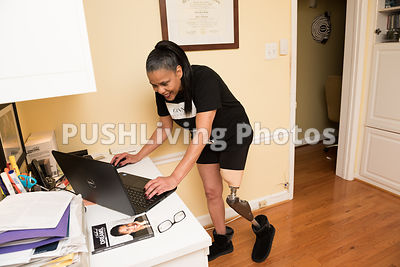 Woman with a prosthetic leg on a computer in her home office