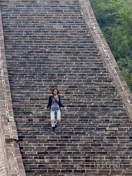 a young woman descends a very steep section of the Great Wall