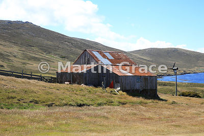 Old wooden farm building with a corrugated iron roof, plus electricity-generating wind turbine, Carcass Settlement, Carcass I...