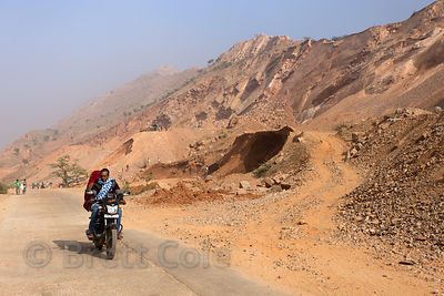 A motorcycle passes a rock mine near Kharekhari village, Rajasthan, India. The mine employs many villagers.