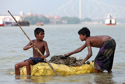 Two boys ride a homemade raft to harvest mud from the Hooghly River in Kolkata, India. They sell balls of the mud to pilgrims...