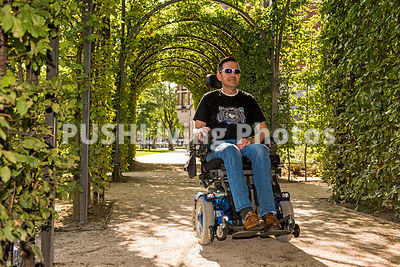 Man using a power wheelchair under a garden arbor