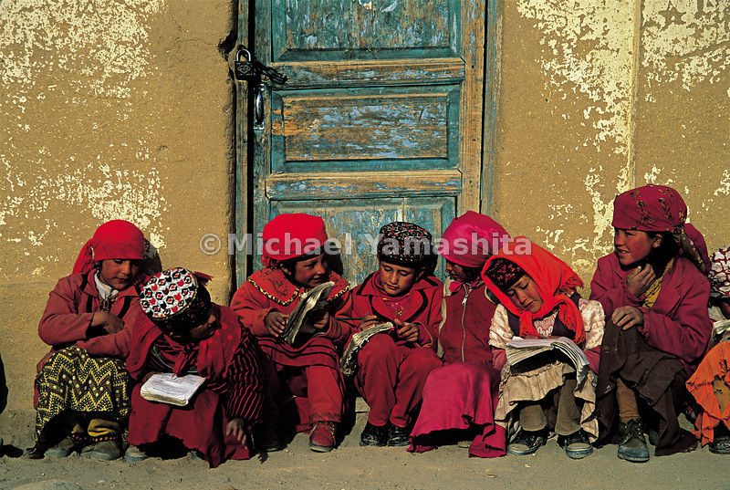 Tajik school girls wait for their lessons to start. In this corner of the world, males wear blue, while females wear red.
