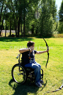 Young boy in a wheelchair archery shooting
