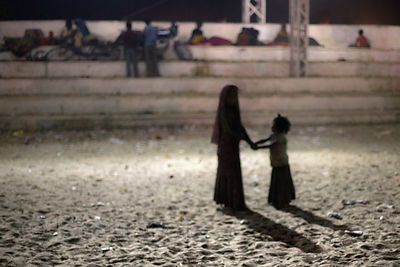Silhouette of children playing in the desert sand at night in the Pushkar stadium, Pushkar, India.