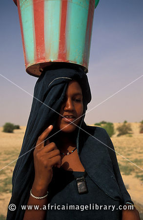 Tuareg woman collecting water from a well in the Sahara desert, Timbuktu, Mali