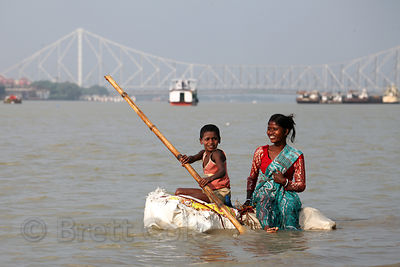 A brother and sister ride a homemade raft to harvest mud from the Hooghly River in Kolkata, India. They sell balls of the mud...